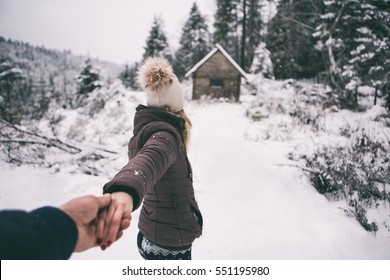 Young couple winter adventures.winter ,Snow isolated.Hold each other hands,girl and her boyfriend walking in forest