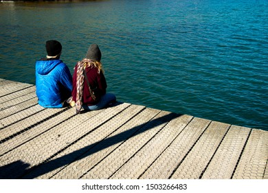 Young couple in winter clothes sitting on wood pier, relax and enjoy remarkable scenery turquoise Wakatipu Lake, best popular location for tourists and photographers in Glenorchy, South New Zealand.