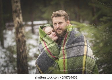 Young couple winter forest walk in a warm blanket
