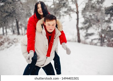 Young couple in a winter park. Man with a red sharf. Lady in a red jacket