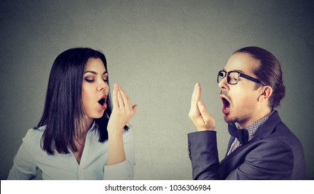 Young couple woman and man checking their breath with hand gesture