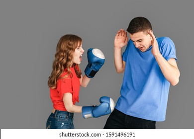 Young couple woman wearing boxing gloves punching man shouting angry standing isolated on grey background