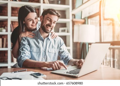 Young couple is working in cafe on laptop and smiling.