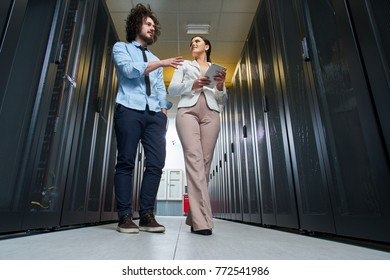 Young couple working at a data center. Black server room.