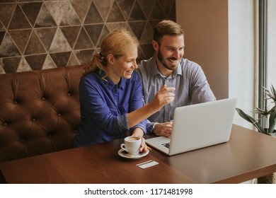 Young couple working on laptop in cafe