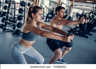 Young couple is working out at gym with weight. Attractive woman and handsome muscular man are training in light modern gym with kettlebell.