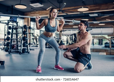 Young couple is working out at gym. Attractive woman and handsome muscular man trainer are training in light modern gym. Beautiful girl squats under the supervision of the coach.
