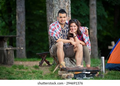 Young couple wrapped in blanket warming up by the fire in front of the tent