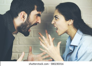 Young couple yelling at each other in studio