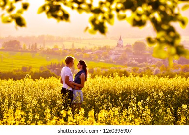 Young couple in yellow colza field. Warm sunset light.