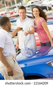 Young coupled collecting new car from salesman