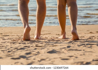 Young couple's barefoot going to swim in cold sunny day. Woman legs have goosebumps. Back view. Closeup.