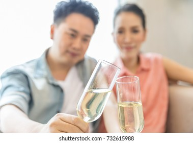 Young Couples celebrate together with wine  in bedroom of contemporary house for modern lifestyle concept (Focus at glasses)