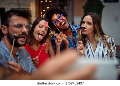 Young couples with funny masks taking a sefie at a party