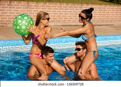 Young couples having fun on summer holiday in swimming pool, laughing.