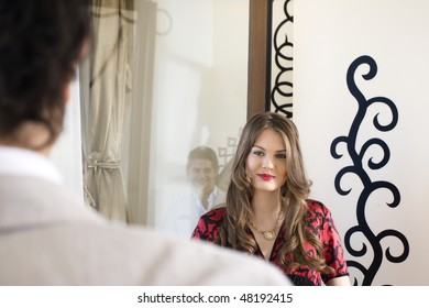 young couples looking each other with love. Reflection of man beside the woman .