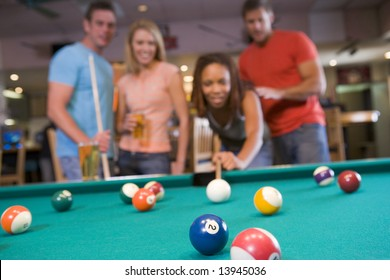 Young couples playing pool in a bar (focus on pool table)