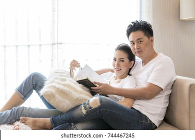 Young Couples reading book tohether in living room of contemporary house for lifestyle concept