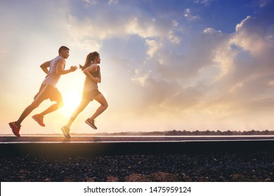 Young couples running sprinting on road. Fit runner fitness runner during outdoor workout with sunset background