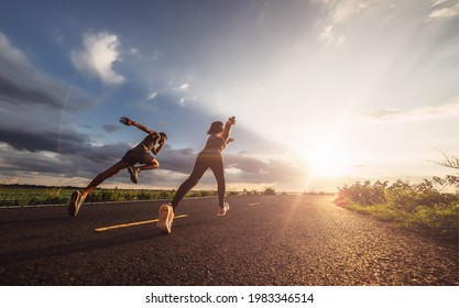 Young couples running sprinting at sunset times. Fit runner fitness runner during outdoor workout.