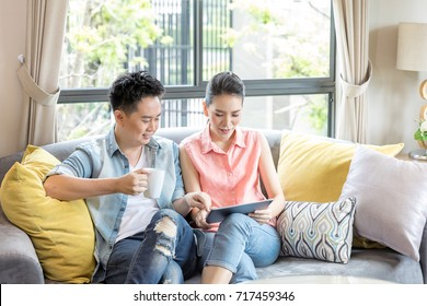 Young Couples using tablet tohether in living room of contemporary house for modern lifestyle concept