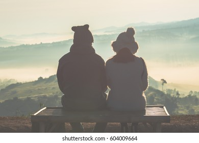 Young couples watch the sunrise on a cold and misty day.