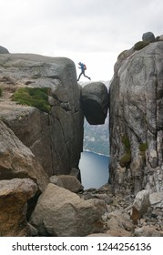 Young courageous man jumping from Kjerag bolten in Norway on a cloudy day of summer