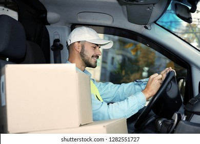 Young courier checking amount of parcels in delivery van