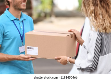 Young courier delivering parcel to woman outdoors