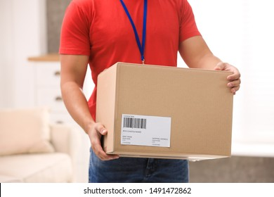 Young courier holding parcel indoors, closeup. Delivery service