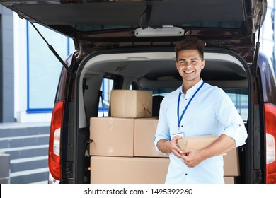 Young courier with parcel near delivery car outdoors