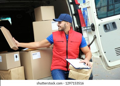 Young courier with parcels and clipboard near delivery van outdoors