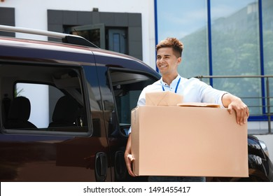 Young courier with parcels near delivery car outdoors