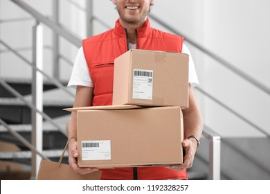Young courier standing with parcels near stairs indoors