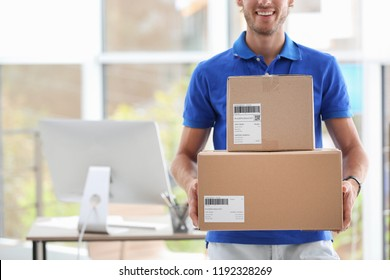 Young courier standing with parcels near office desk. Space for text