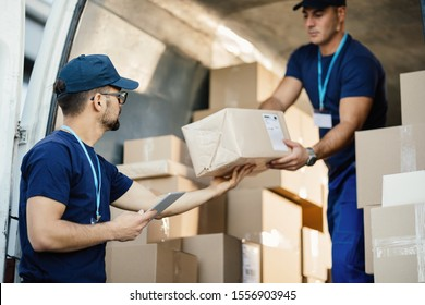 Young courier using touchpad while loading packages with his coworker in a delivery van.