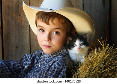A young cowboy with big brown eyes and a barn cat with blue eyes