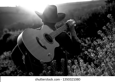 a young cowboy with his guitar at the countryside of Texas on a sunset evening