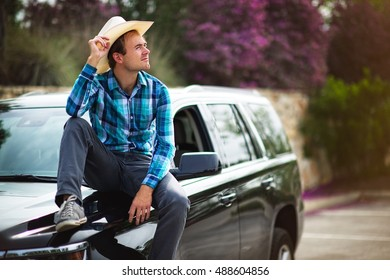 A young cowboy keeping his hat and sitting on his truck.