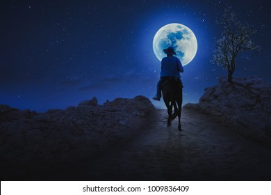 A young cowboy rides along the path in the full moon night.
