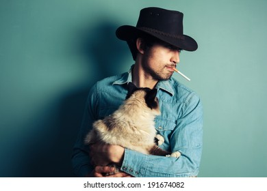 A young cowboy is smoking a cigarette and holding a cat