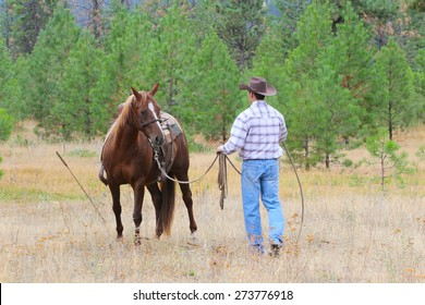 Young cowboy working with his horse in the field