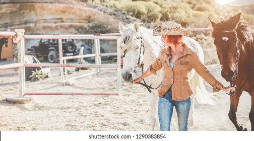 Young cowgirl preparing horses for training inside finca's corral - Farmer woman working inside equestrian ranch - Culture, wildlife, healthy lifestyle, sport concept - Focus on woman face