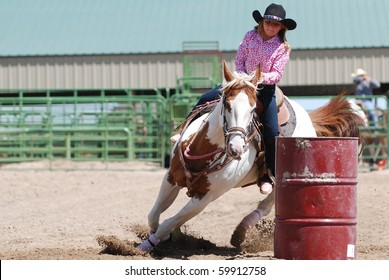 Young cowgirl riding a beautiful paint horse in a barrel racing event at a rodeo.