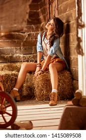 young cowgirl sits on a bale of hay, with a slight snob expression. Cowgirl sitting on hay in the stable
