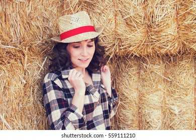 Young cowgirl wearing a  plaid shirt and wheat hat