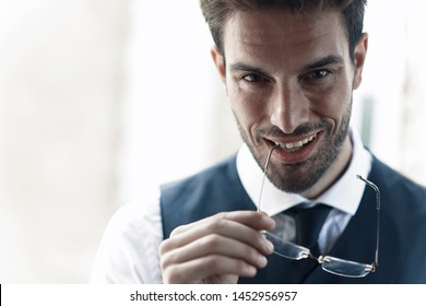 Young coworker flirting and looking sexy, biting his glasses