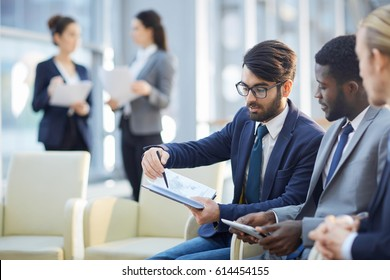 Young co-workers discussing notes of businessman after lecture or conference