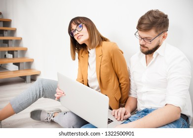 Young coworkers using laptop in office