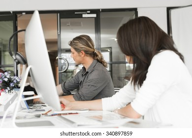 Young coworkers working together and discussing points while using computer